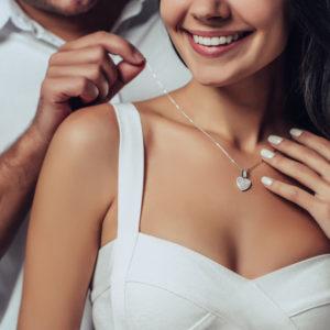 femme qui met un bijou collier offert en cadeau