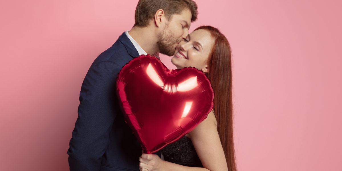 homme qui embrasse sa femme qui tient un ballon coeur pour la saint valentin