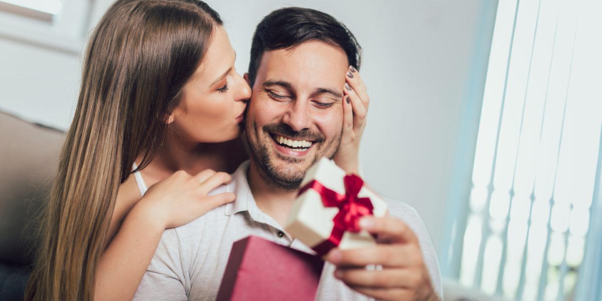 Homme qui ouvre un cadeau sensuel offert par sa femme pour la saint valentin