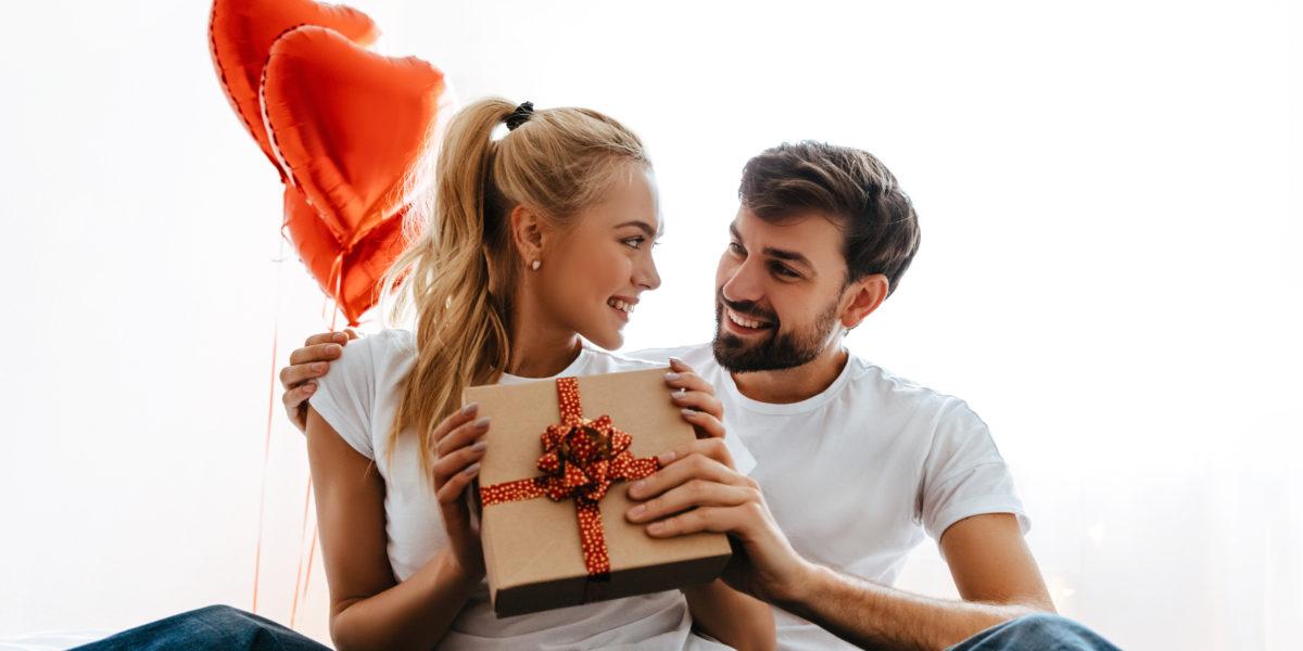 couple pendant la saint valentin une femme tient un cadeau de luxe